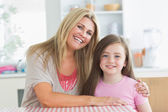 Mother and little girl smiling and embracing — Stock Photo