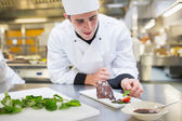 Cheerful chef putting mint with his dessert — Stock Photo