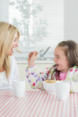 Girl feeding her mum cereal — Stock Photo