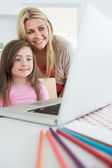 Mother standing behind daughter looking at laptop — Stock Photo