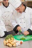 Chef-kok onderwijzen groep hoe slice groenten — Stockfoto
