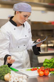 Chef consulting digital tablet before preparing vegetables — Stock Photo