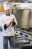 Smiling chef holding a pepper mill — Stock Photo