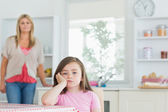 Child at kitchen table looking angry — Stock Photo
