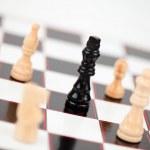 zwarte koningin omgeven door witte schaakstukken — Stockfoto