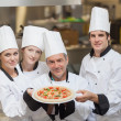 Four Chef's holding a pizza — Stock Photo
