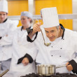 Smiling chef tasting his students work — Stock Photo