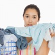 Frowning woman taking out dirty laundry — Stock Photo #23111144