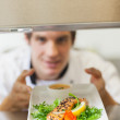Chef handing salmon dinner through order station — Stock Photo