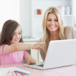 Daughter pointing at laptop with mother — Stock Photo #23111546