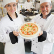 Foto Stock: Chef's presenting pizza