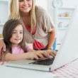 Little girl typing with mother watching at laptop — Stock Photo #23111956