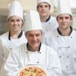 Chef presenting pizza with others behind him — Stock Photo #23112208