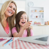 Mother and daughter laughing at laptop — Stock Photo