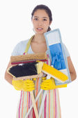 Frowning woman holding brushes and mops — Stock Photo