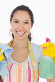Happy woman holding spray bottle and rag — Stockfoto