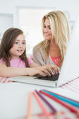Little girl typing with mother smiling — Stock Photo