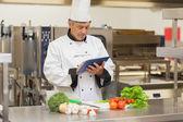 Chef-kok voorbereiding recept met digitale tablet — Stockfoto