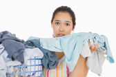 Frowning woman taking out dirty laundry — Photo