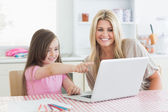 Daughter pointing at laptop with mother — Stock Photo
