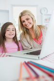 Mother and girl are smiling at the kitchen — Stock Photo