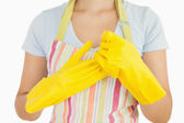 Woman taking off her rubber gloves — Stock Photo