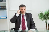 Businessman phoning in his office — Stock Photo