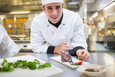 Smiling chef putting mint with his dessert — Stock Photo