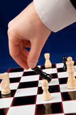 Hand holding black chessman — Stock Photo