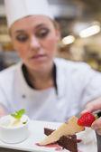 Chef putting strawberry on dessert plat — Stock Photo