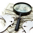 Stock Photo: Handcuffs dollars and magnifying glass
