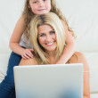 Daughter hugging her mother using laptop — Stock Photo