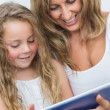 Royalty-Free Stock Photo: Mother and daughter having fun with tablet computer