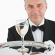 Smiling man serving glass of wine on platter — Stock Photo