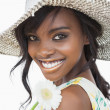 Womsmiling and holding white flower in sun hat — Stock Photo #23487855