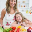 Mother and daughter standing at the table — Stock Photo #23488297