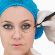 Plastic surgeon writing on woman's face — Stock Photo