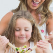 Close up of mother and daughter during mixing salad — Stock Photo