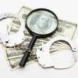 Magnifying glass money and handcuffs — Stock Photo