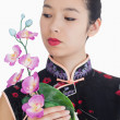 Woman in kimono holding orchid — Stock Photo