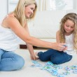 Daughter and mother doing a jigsaw — Stock Photo