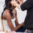 Stock Photo: Womsitting while getting makeup done
