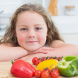 Girl leaning beside vegetables — Stock Photo #23489871
