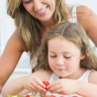 Mother looking at daughter preparing vegetables — Stock Photo #23489963