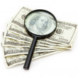Magnifying glass resting on dollars — Stock Photo
