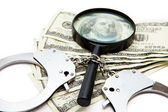 Handcuffs dollars and a magnifying glass — Stock Photo