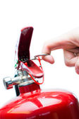 Hand pulling safety pin from fire extinguisher — Stock Photo