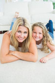 Mother and daughter resting on the carpet — Stock Photo
