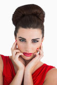 Woman touching her face and looking serious — Stock Photo