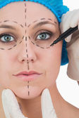 Doctor drawing on woman's face for face lift — Stock Photo